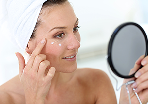 skin care products   attractive woman applying lotion to face